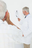 Pediatrician ophthalmologist with senior patient pointing at eye chart Stock Images