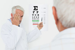 Pediatrician ophthalmologist with senior patient pointing at eye chart Stock Photo