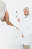 Pediatrician ophthalmologist with senior patient pointing at eye chart Stock Image