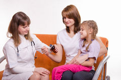 Pediatrician pours medicine into a spoon, which holds mother of sick child Royalty Free Stock Image