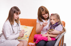 Pediatrician prescribes treatment child whose mother gives to drink tea from a spoon Royalty Free Stock Image