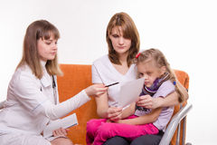 Pediatrician prescribes treatment to child and her mother explains recipe Royalty Free Stock Photo