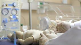 A pediatrician putting an oxygen mask on a newborn infant.