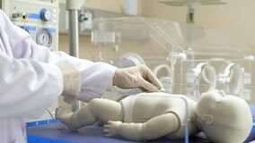 A pediatrician putting a skin probe on a newborn infant.