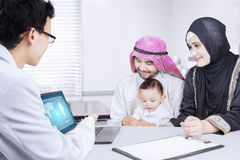 Pediatrician showing a medical report to his patient. Picture of pediatrician showing a medical report to Muslim family on a laptop while sitting in the clinic Stock Image