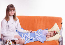 Pediatrician sitting at the bedside of a sick child Royalty Free Stock Images