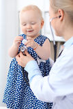 Pediatrician is taking care of baby in hospital. Little girl is being examine by doctor with stethoscope Stock Photography