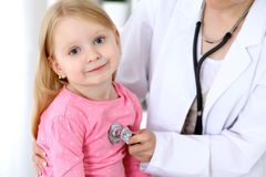Pediatrician is taking care of baby in hospital. Little girl is being examine by doctor by stethoscope. Health care. Insurance and help concept Stock Photography