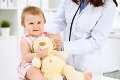 Pediatrician is taking care of baby in hospital. Little girl is being examining by doctor with stethoscope. Health care royalty free stock photos