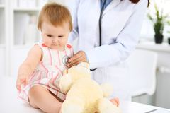 Pediatrician is taking care of baby in hospital. Little girl is being examining by doctor with stethoscope. Health care. Insurance and help concept Royalty Free Stock Photo