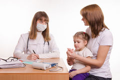Pediatrician talking in office with a young mother with child on her lap Royalty Free Stock Photo