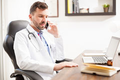 Pediatrician talking on the phone in an office Royalty Free Stock Photography