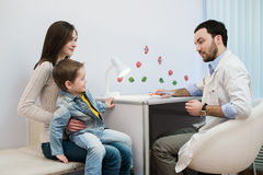 Pediatrician talking to mother and child at office Stock Images