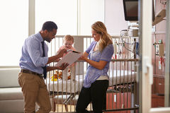Pediatrician Visiting Mother And Child In Hospital Bed Royalty Free Stock Photography