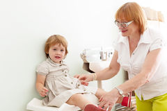 Pediatrician weighs the baby Stock Images