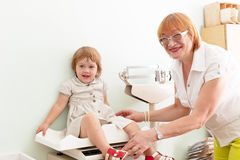 Pediatrician weighs the baby Stock Photography