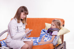 Pediatrician writes complaints sick girl Royalty Free Stock Photo