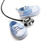 Pediatrics. Baby shoes with stethascop against a white background Royalty Free Stock Image