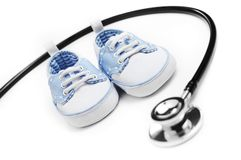 Pediatrics. Baby shoes with stethascop against a white background Stock Images