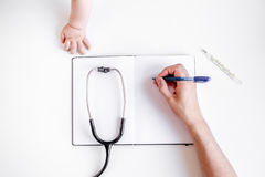 Pediatrics equipment with child hand, copybook white background top view space for text Stock Photography
