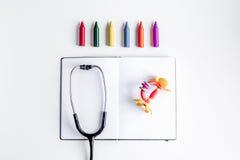 Pediatrikutrustning med färgpennor, utrymme för bästa sikt för bakgrund för förskriftsbok vitt för text royaltyfri foto