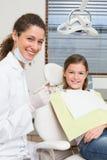 Pediatrisch tandarts en meisje als tandartsenvoorzitter die bij camera glimlachen Stock Afbeelding