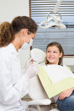 Pediatrische tandarts die met meisje als tandartsenvoorzitter spreken Stock Afbeelding