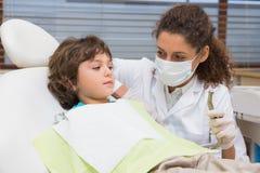 Pediatrische tandarts die weinig jongen als voorzitter de boor tonen Royalty-vrije Stock Foto