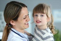 Pediatrisk doktor som rymmer och kramar den lilla gulliga flickapatienten royaltyfri bild