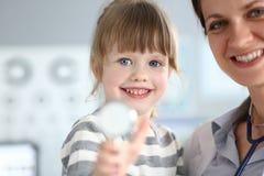 Pediatrisk doktor som rymmer och kramar den lilla gulliga flickapatienten arkivbilder
