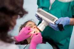 Pediatrisk tandläkare med assistenten som gör den tålmodiga flickan för tand- behandling som använder den tand- röntgenapparaten  Arkivbild