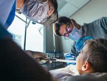 Pediatrisk tandläkare som gör tand- behandling på pys arkivfoto