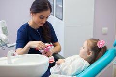Pediatrisk tandläkare som utbildar en le liten flicka om riktigt tand-borsta som visar på en modell tidigt royaltyfri bild