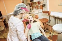Pediatrisk tandläkekonst Tandläkaren behandlar tänder av lilla flickan royaltyfria bilder