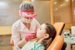 Pediatrisk tandläkekonst Tandläkaren behandlar tänder av lilla flickan fotografering för bildbyråer
