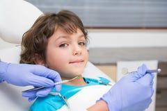 Pediatrisk tandläkare som lite undersöker pojketänder i tandläkarestolen Arkivbild