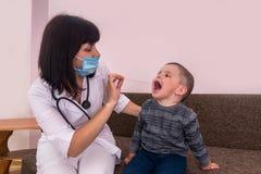 Pediatrisk undersökande hals för doktor av pysen arkivfoton