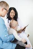 Pediatriska With Digital Tablet som ser, behandla som ett barn rymt av kvinnan Arkivbild