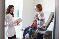 Pediatriska Meeting With Mother och barn i examenrum arkivfoton