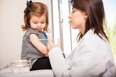 Pediatriskt ge en flicka ett skott arkivbild