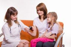 Pediatriskt häller medicin in i en sked, som rymmer modern av det sjuka barnet Royaltyfri Bild