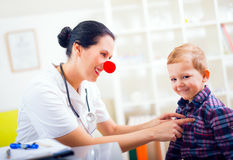 Pediatriskt med clownnäsan och den lyckliga barnpatienten Arkivfoton