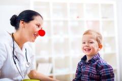 Pediatriskt med clownnäsan och den lyckliga barnpatienten Arkivbild