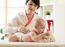 Pediatriskt undersöka behandla som ett barn Doktorn som använder stetoskopet, lyssnar för att lura tillbaka att kontrollera hjärt Royaltyfria Bilder