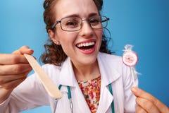 Pediatrist arts met lolly die spatel gebruiken om keel te onderzoeken stock foto