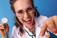 Pediatrist woman with stethoscope distracting child playing Royalty Free Stock Photo