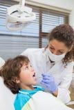 Pediatryczny dentysta egzamininuje troszkę chłopiec zęby w dentysty krześle zdjęcie royalty free