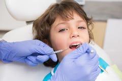 Pediatryczny dentysta egzamininuje troszkę chłopiec zęby w dentysty krześle obrazy stock