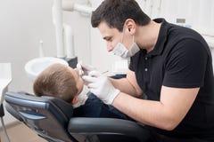 Pediatryczny dentysta egzamininuje zęby chłopiec pacjent w stomatologicznej klinice używać stomatologicznych narzędzia - sonda i  Zdjęcie Stock