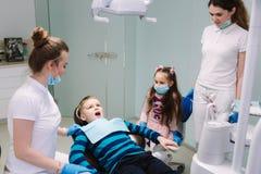 Pediatryczny dentysta z asystentem z ch?opiec i dziewczyn? zdjęcia stock